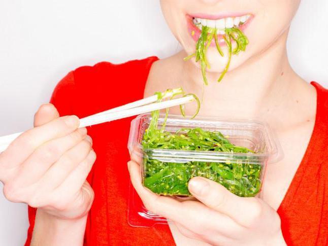 Женщина ест морскую капусту